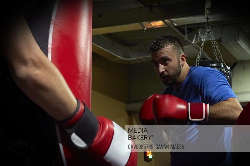 Side view of confident male boxer exercising at punch bag in gym