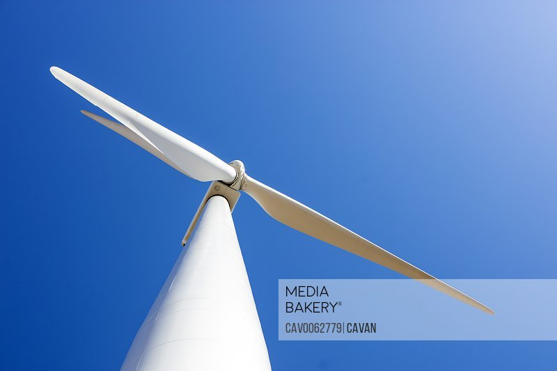 Looking up at wind turbine against blue sky