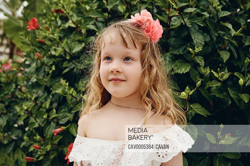 Cute girl near blooming shrub