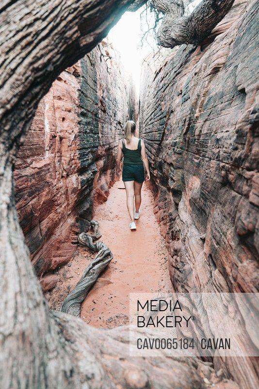 Young female hiking through narrow canyon in Utah
