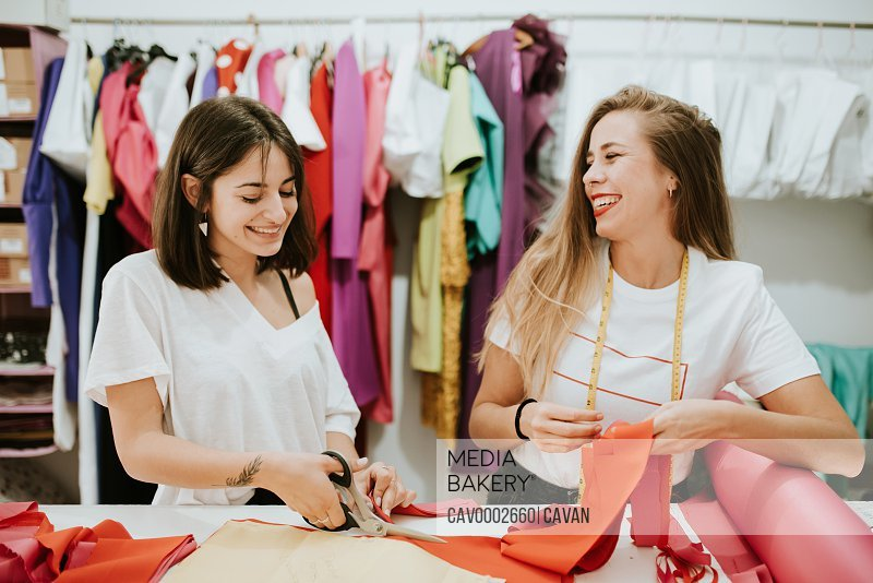 Two women having fun together at work. fashion designers