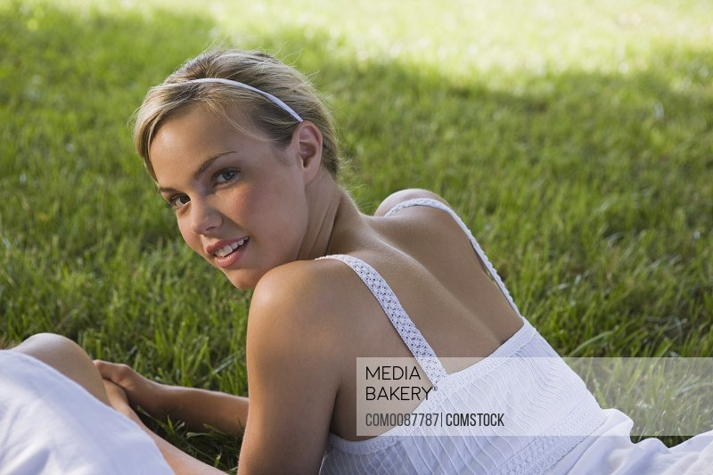 Content woman lying on grass