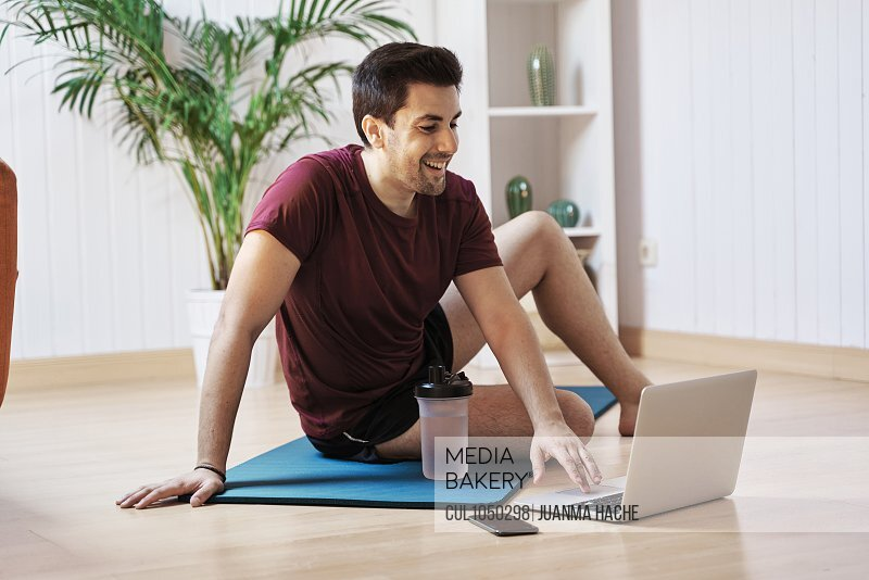 Man on exercise mat at home, using laptop