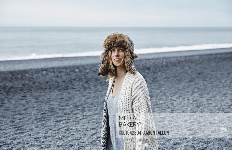 A woman wearing a fur lined hat looking at the camera standing on a grey stony beach with the sea in the background.