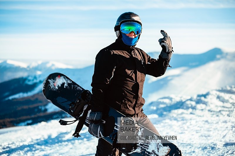 A person wearing a black ski suit, helmet and goggles holding a snowboard standing on top of a snowy mountain.