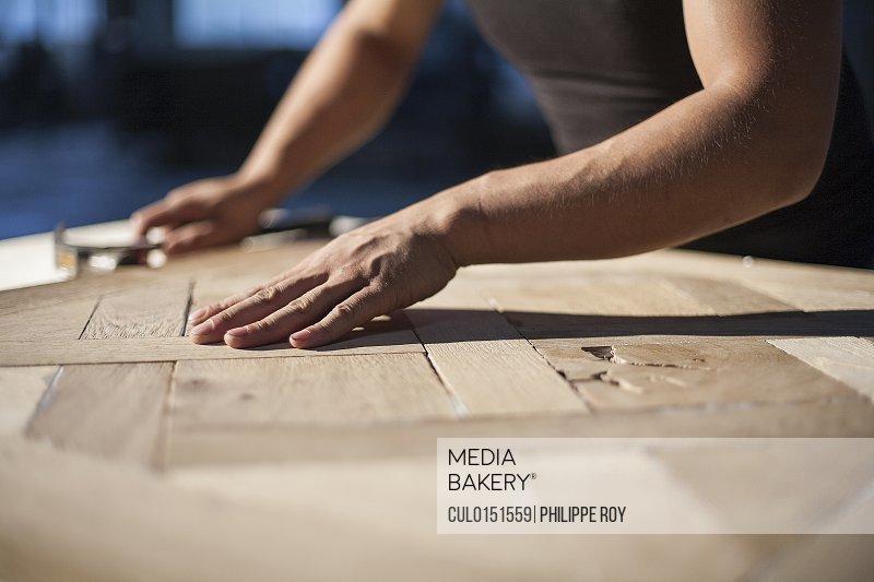 Carpenter piecing together wood blocks in factory Jiangsu China