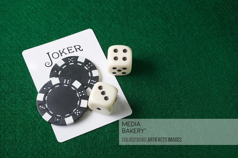 Joker card and gambling chips and dice