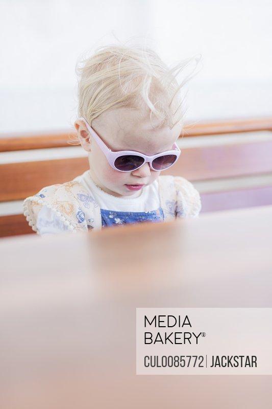Toddler girl wearing sunglasses indoors