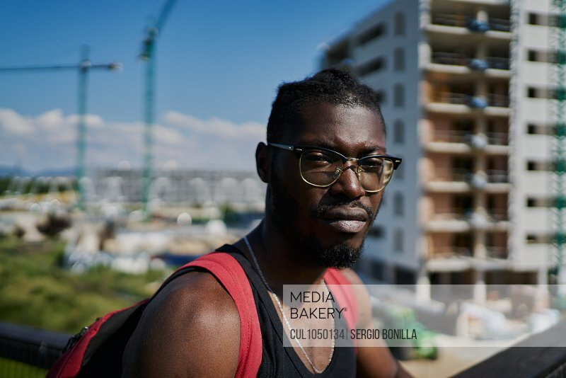 Young man wearing glasses, buildings in background
