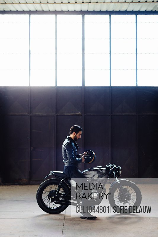 Young male motorcyclist straddling vintage motorcycle in empty warehouse, full length