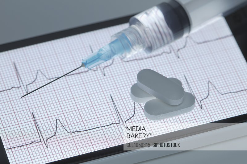 Pills and a syringe on the screen of a smartphone that displays a healthy electrocardiogram