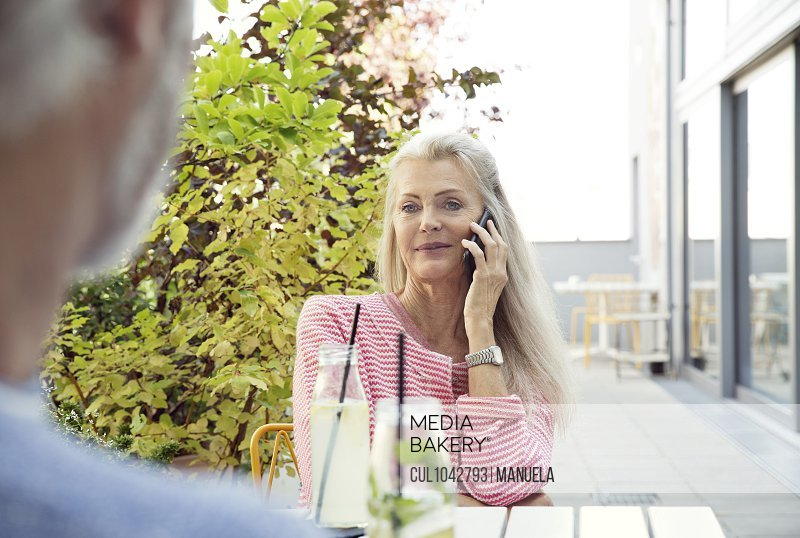 A couple sitting at a table, the woman facing the camera on a mobile phone.