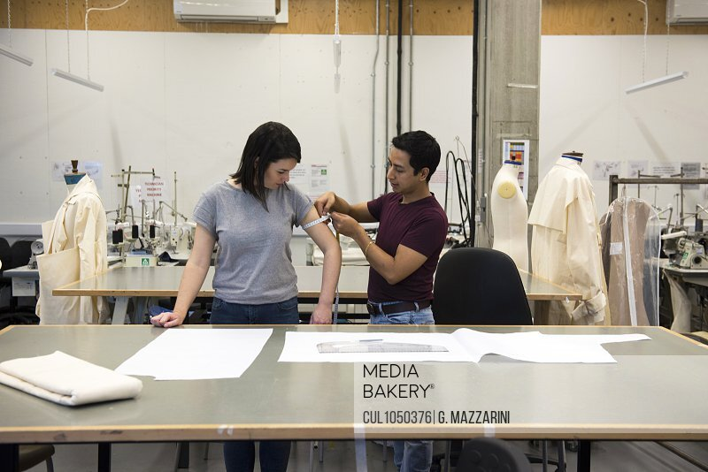 Fashion students, man measuring woman's arm