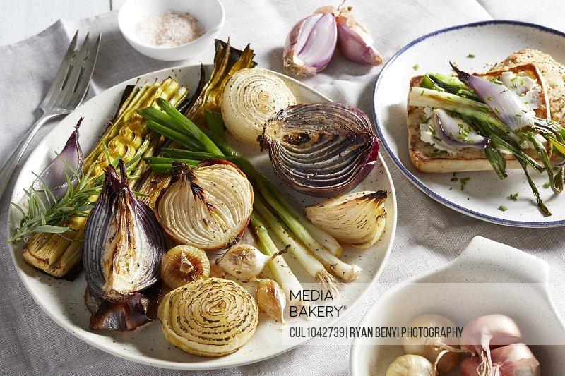 Plates and dishes with a variety of roasted onions, a selection of onions on toast and uncooked shallots in a bowl.