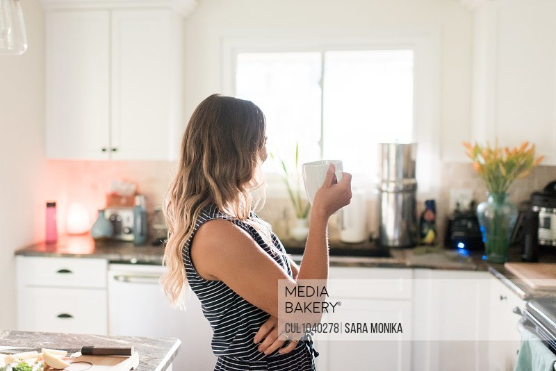 Woman enjoying cup of hot beverage in kitchen