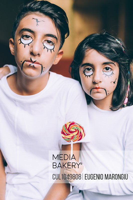 Brother and sister with Halloween face paint, holding lollipop
