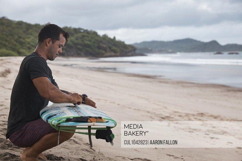 A man crouching on a Nicaraguan beach preparing his surfboard.