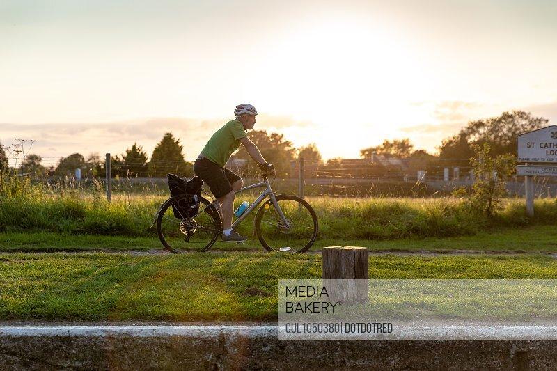 Man cycling along canal path
