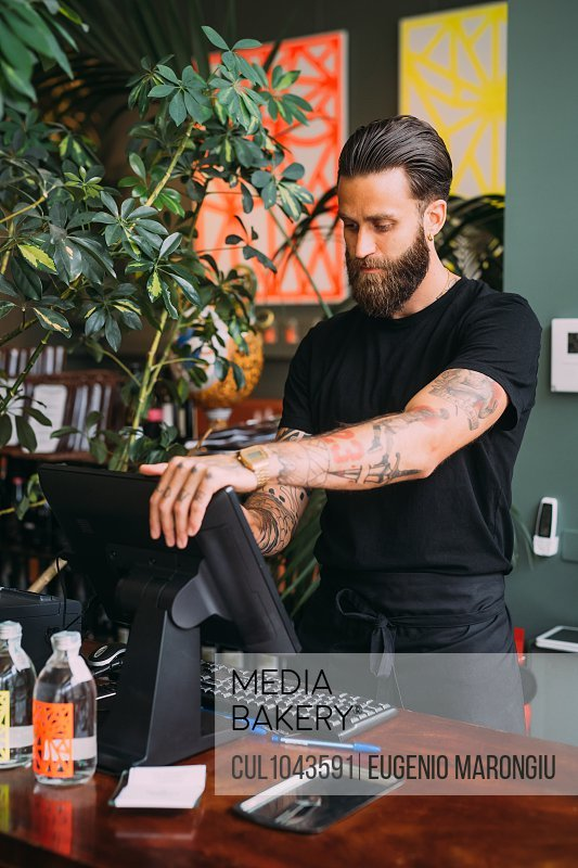 Bearded, tattooed bartender standing at counter, using computerized till.