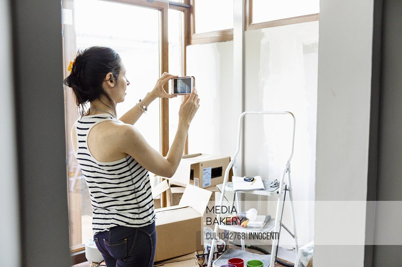 A woman taking a photograph with her mobile phone with a stepladder and cardboard boxes in the room.