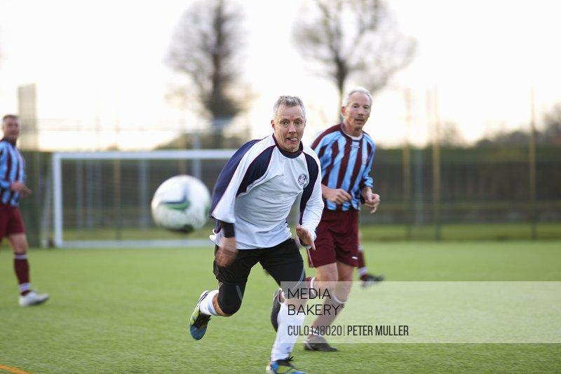 Football players running after ball