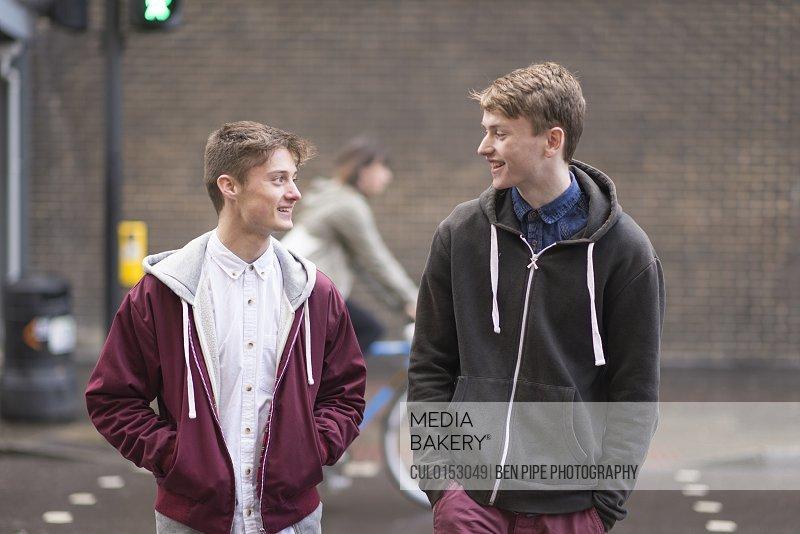 Two male friends crossing road