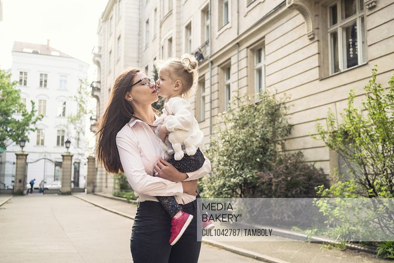 A mother holding her daughter and giving her a kiss in a street setting in Berlin.