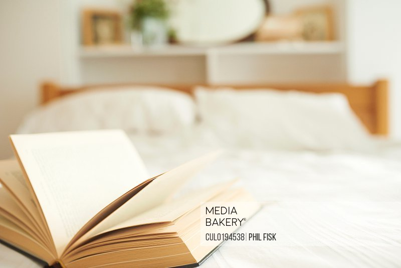 Open book on top of bed