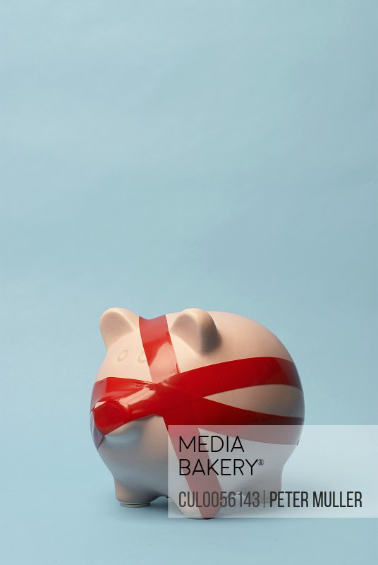 Piggy bank wrapped in red tape