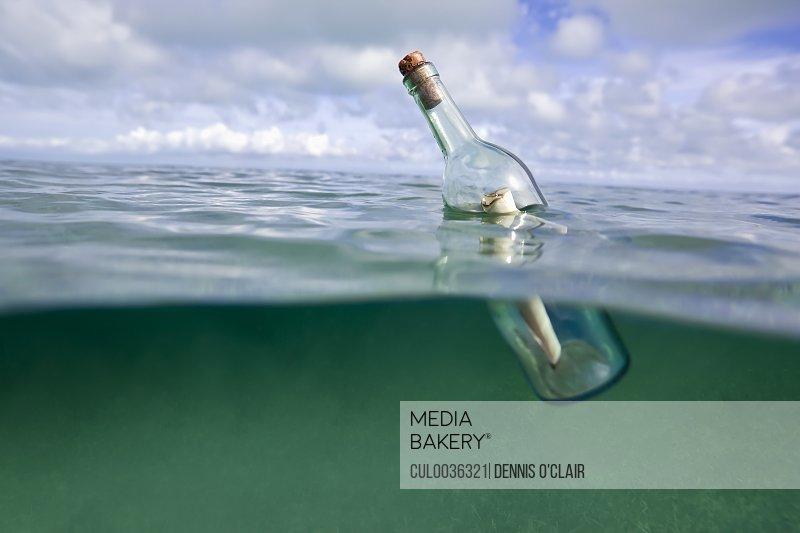 Message in a bottle floating in ocean