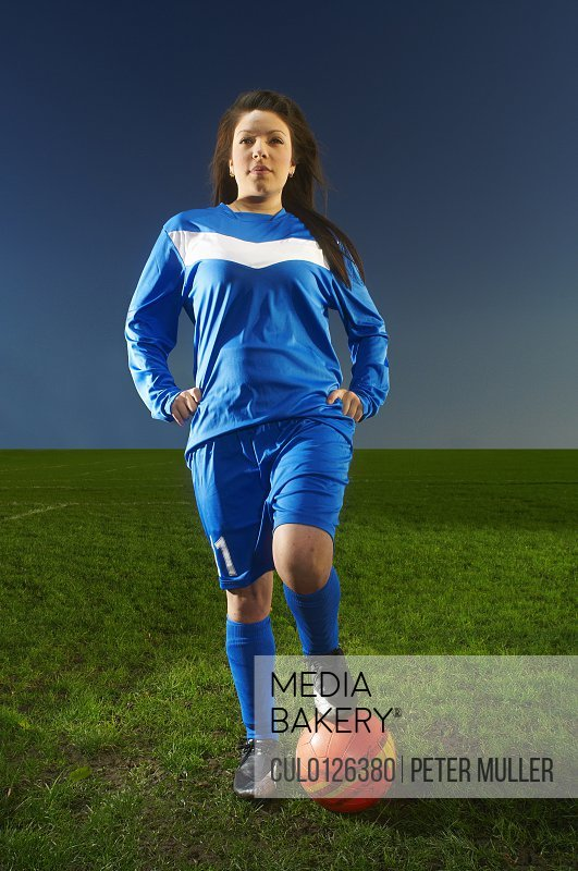 Portrait of female footballer with foot on ball
