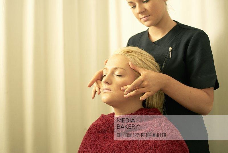 Beautician giving face massage