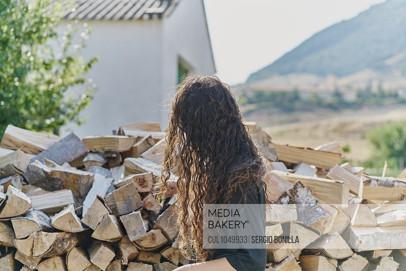 Young woman with long hair, by log pile, side view