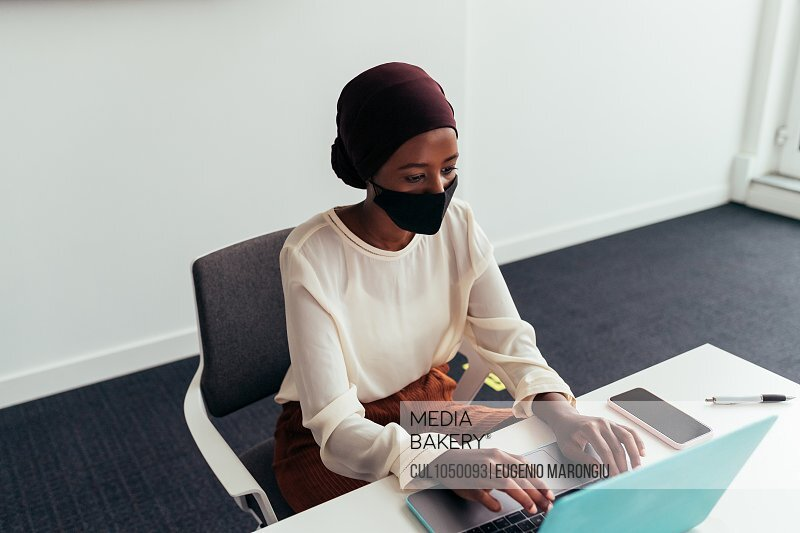 Woman working on laptop, wearing face mask
