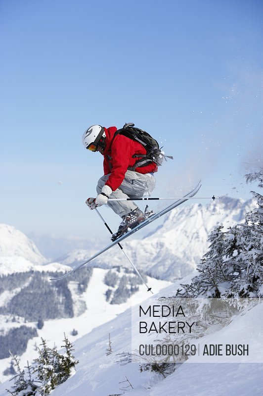 male skier jumping past trees on slope