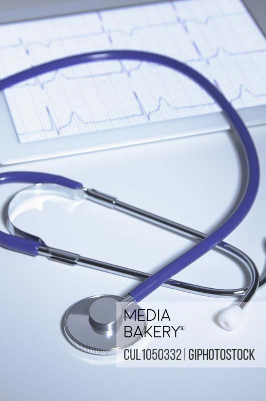Acoustic stethoscope over digital tablet displaying electrocardiogram