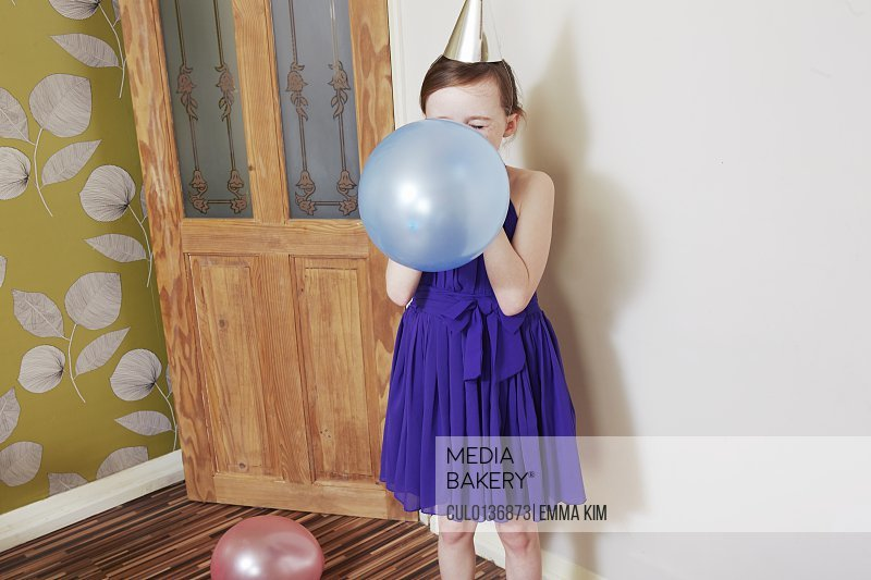 Girl blowing up blue balloon