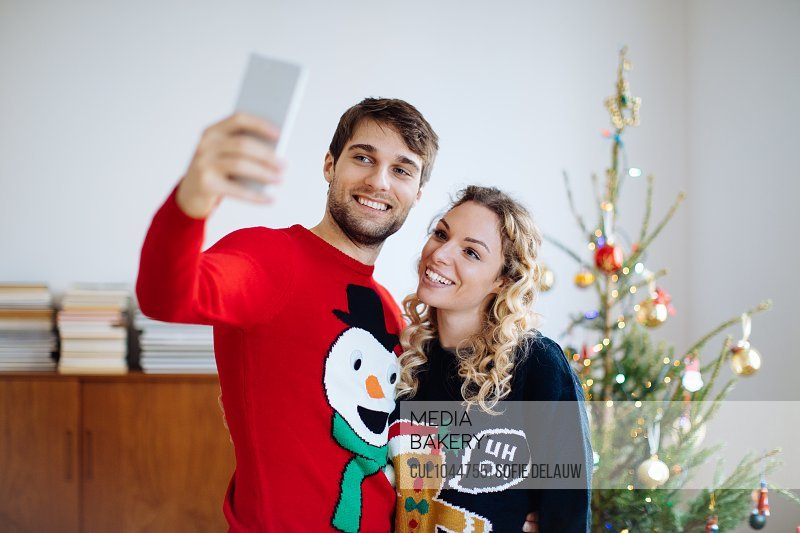 Couple taking selfie in front of Christmas tree at home