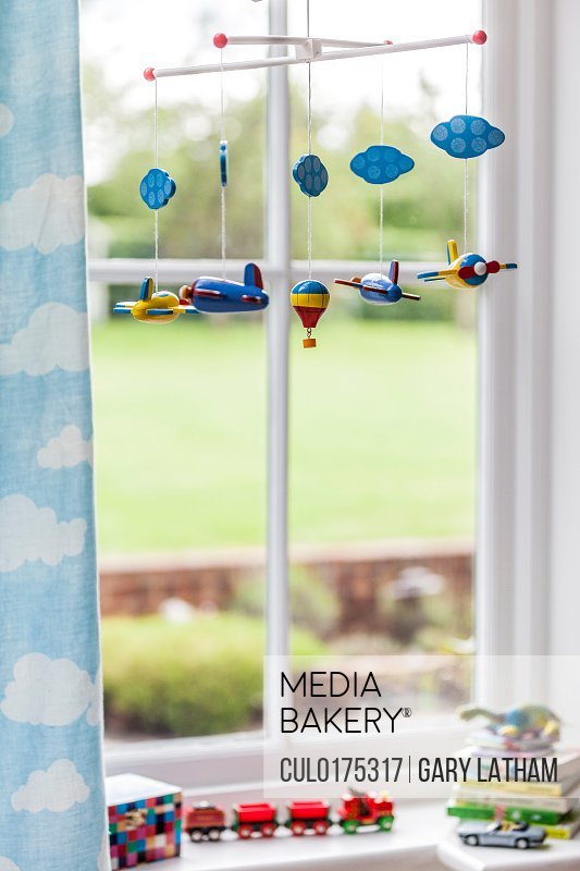 Toy airplane mobile at childs bedroom window
