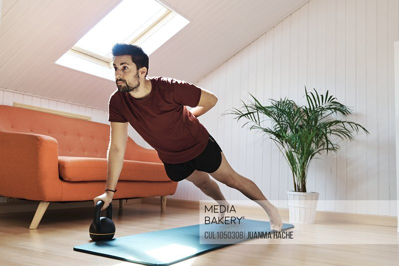 Man exercising at home, push up with kettlebell