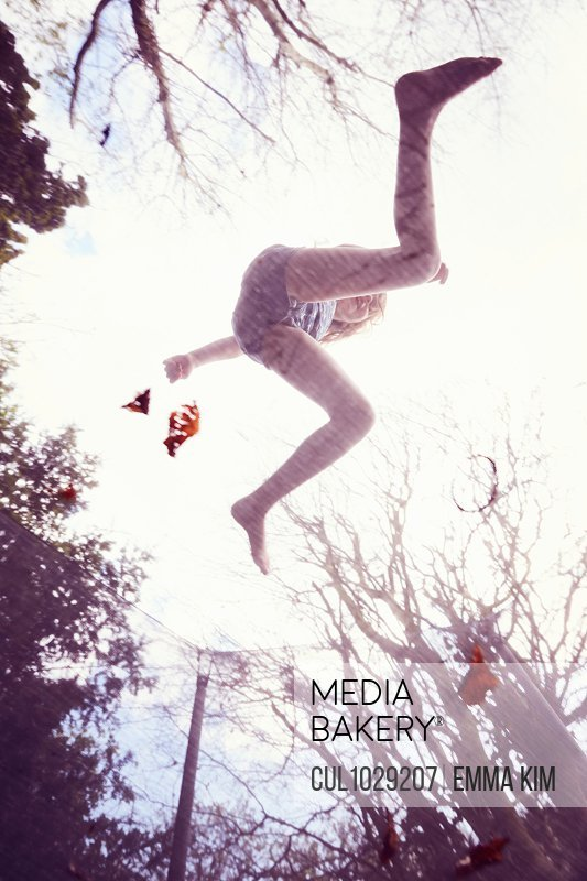 Girl jumping on trampoline, low angle view