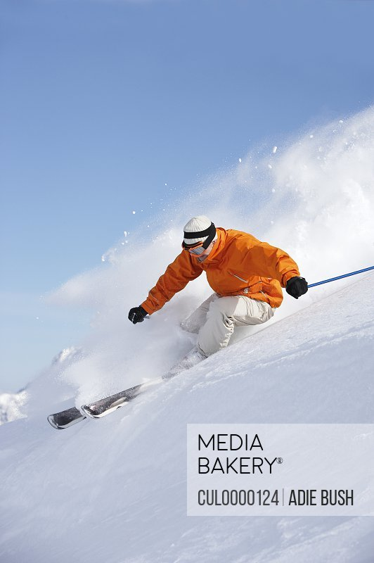 Man skiing down snow mountain slope sending up spray