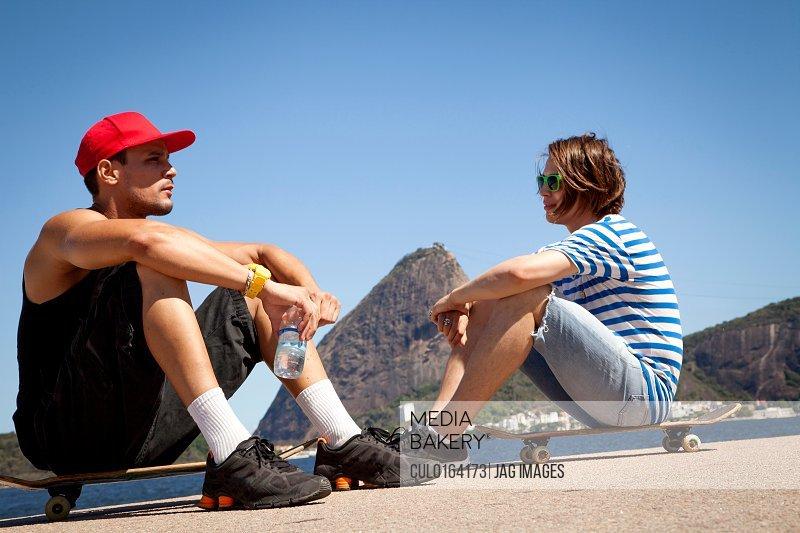 Two men sitting on skateboards relaxing