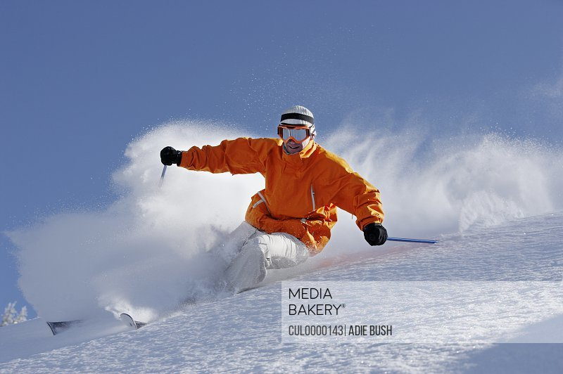 man wearing goggles skiing down slope