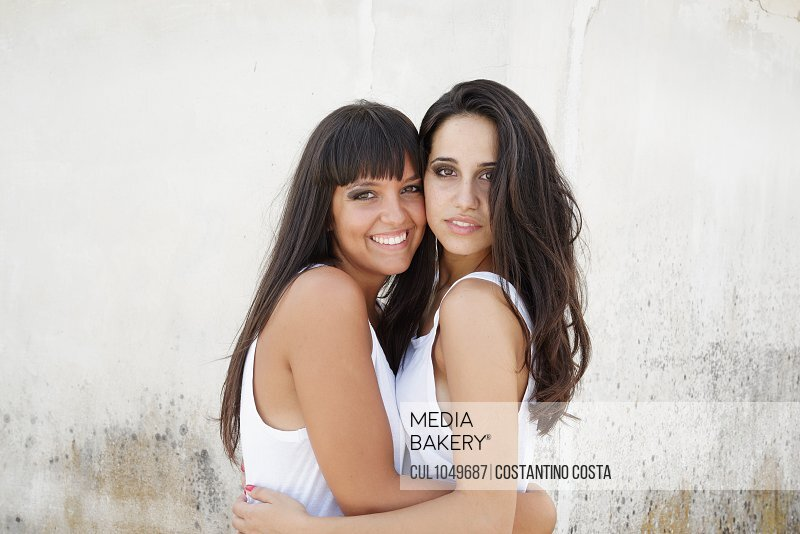 Portrait of two beautiful young women with long brown hair, hugging and smiling at camera.
