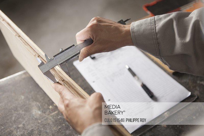 Carpenter measuring wood plank with vernier caliper in factory Jiangsu China