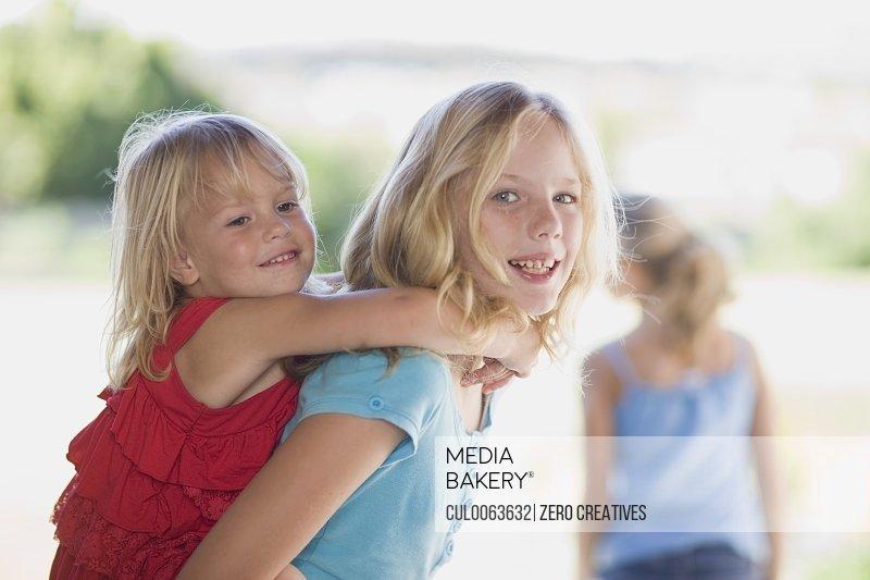 Girl carrying younger sister piggyback