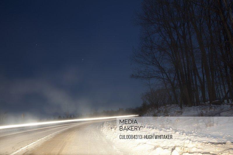 Long exposure of car on snowy rural road
