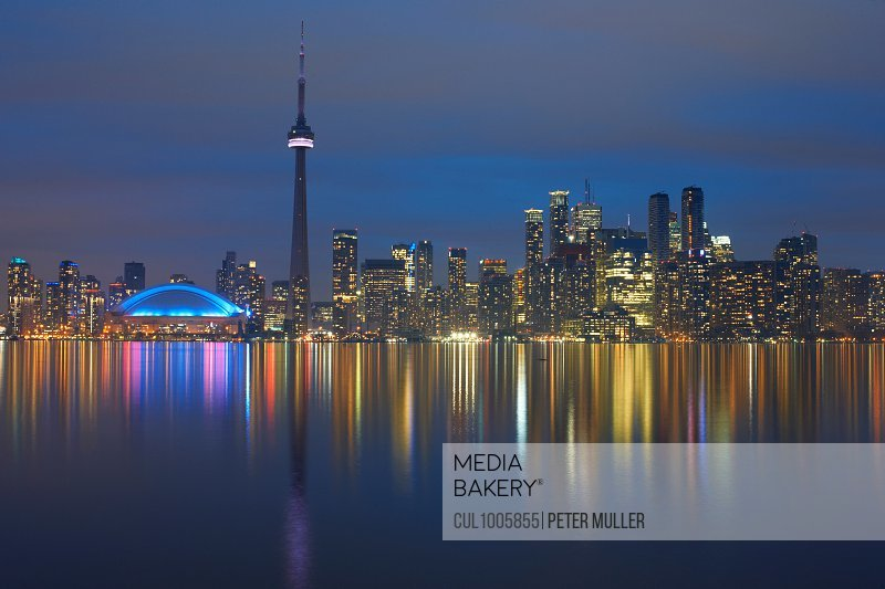 Reflection of skyline in water illuminated at night, Toronto, Canada