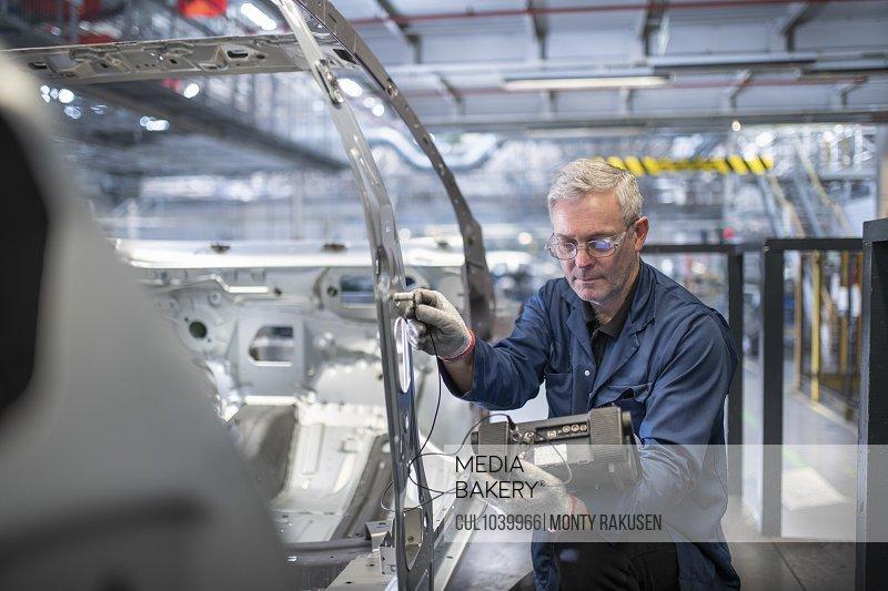 Engineer testing car body in car factory